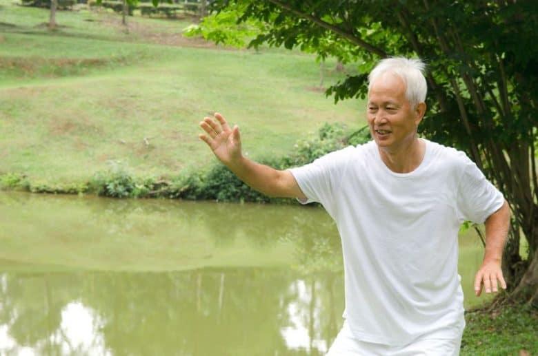 Older Asian man doing Tai Chi