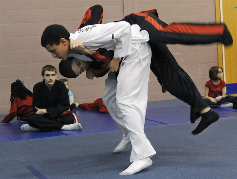 boy in white is Judo throwing a boy in black with red stripe suit