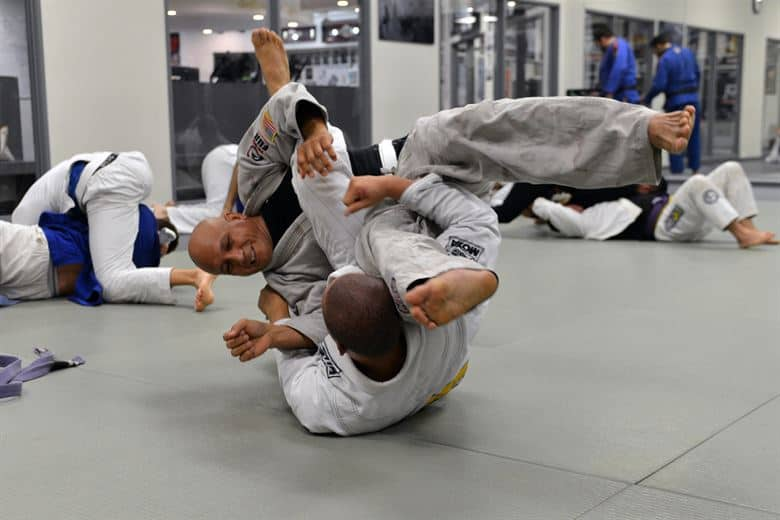 Two men practicing BJJ one in white on the bottom of one in grey