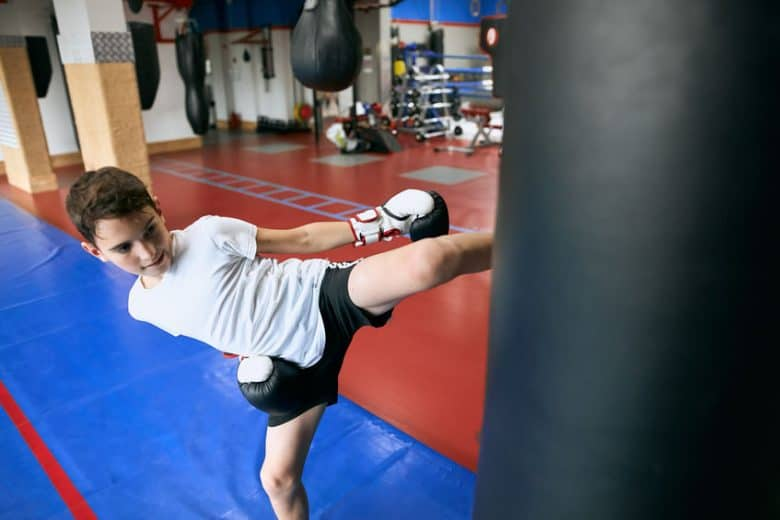 Boy in white shirt and black shorts with boxing gloves kicking a heavy bag