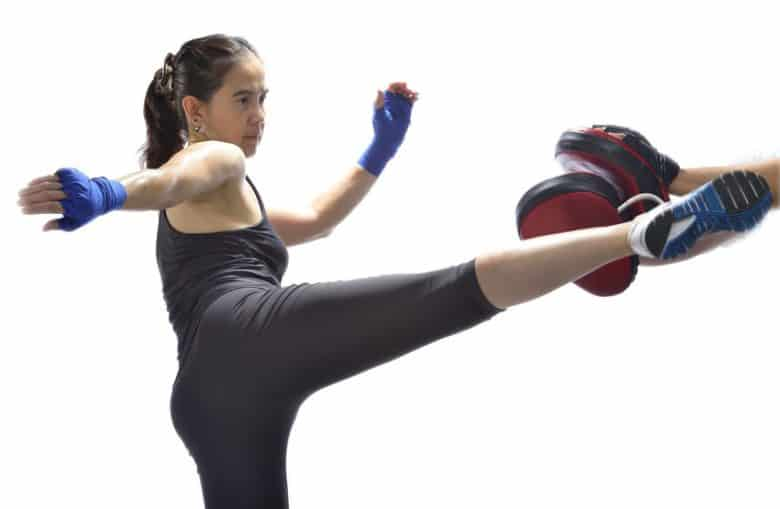 young lady in black clothes and blue hand wraps kicking pads