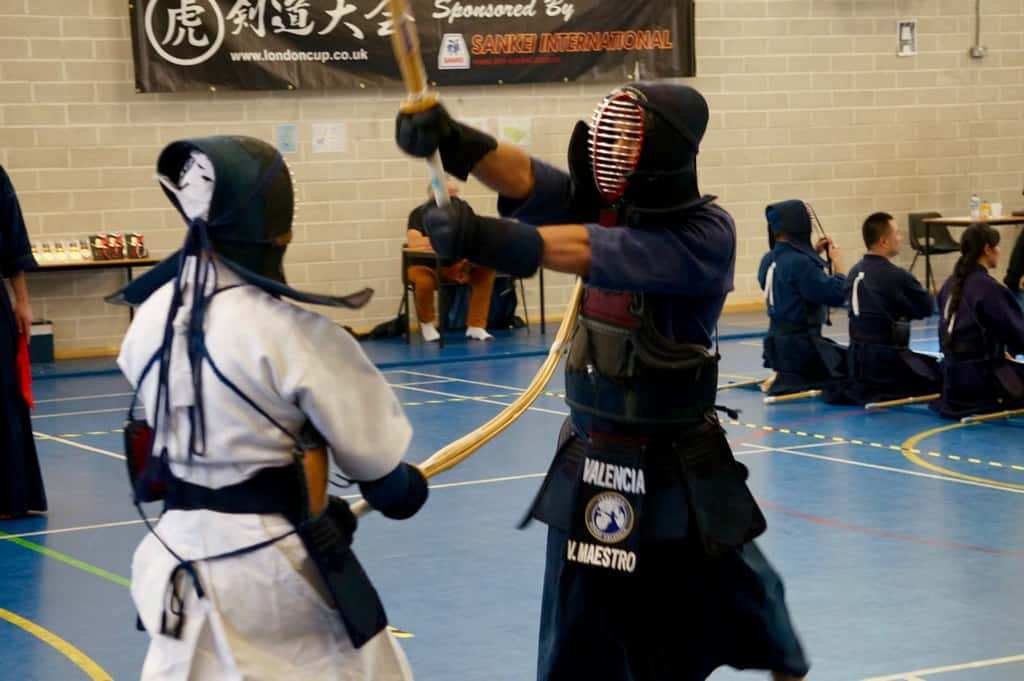 White dressed kendo competitor striking a black dressed opponent