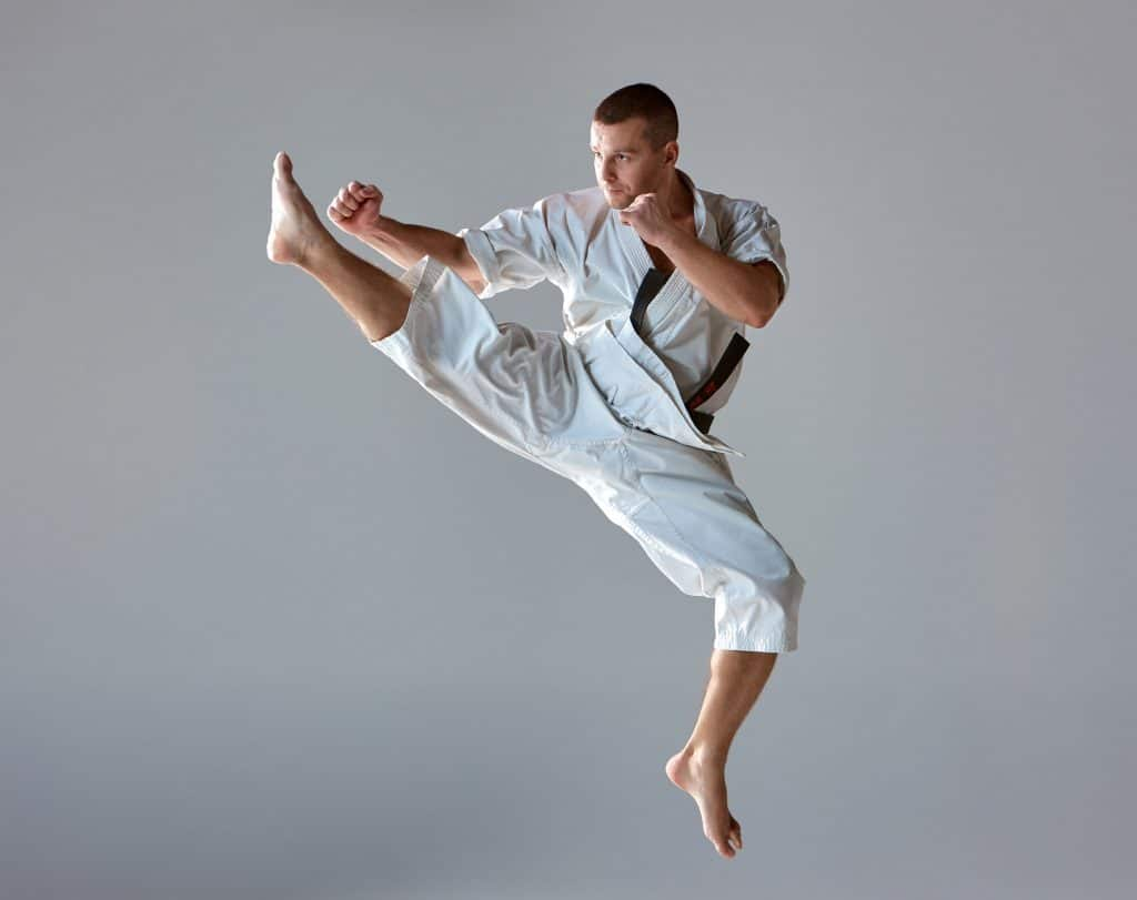 Man in white outfit doing a flying high kick on his own against a grey background