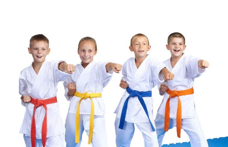 Four boys in white gi and different colour belts punching with left hands