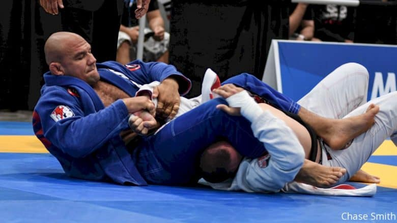 One man in blue attempting to arm bar a man in white gi