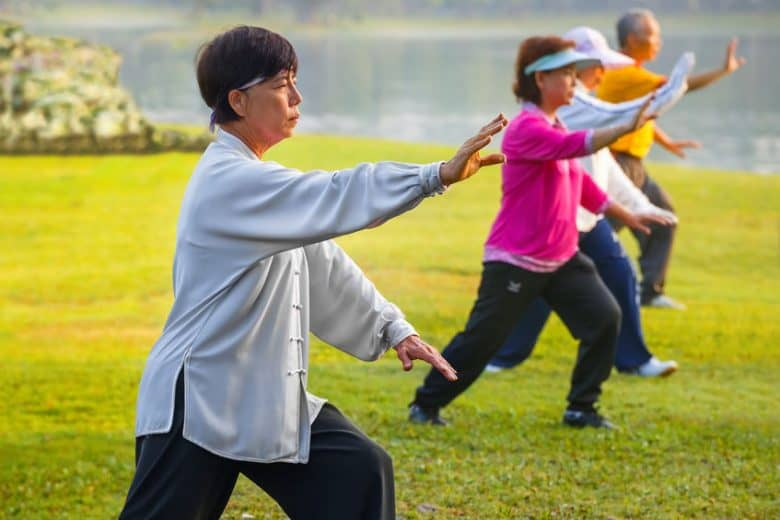 Women doing tai chi on in white and another in pink top