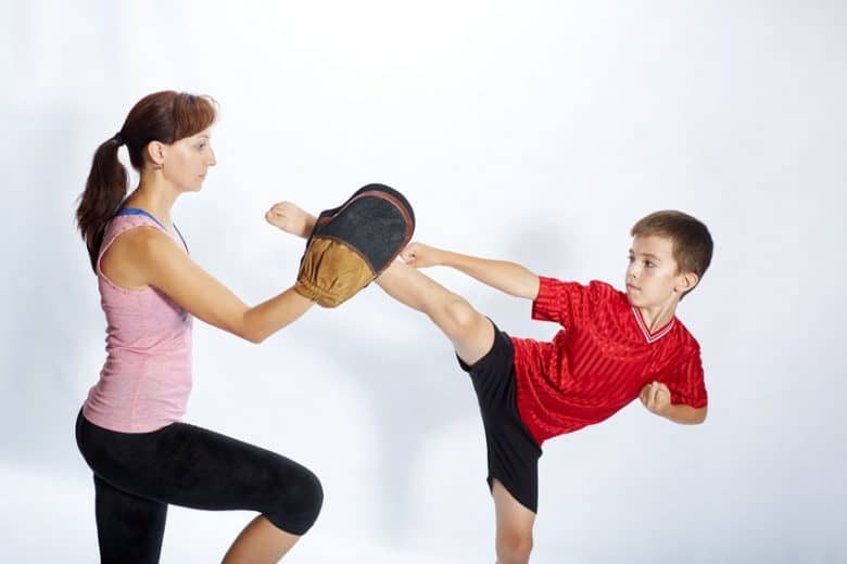 boy in red shirt kicking a pad held by woman in pink top