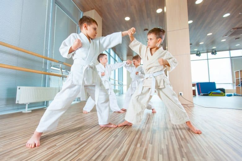 kids in white gi and white belts practicing punching and blocking each other in a row