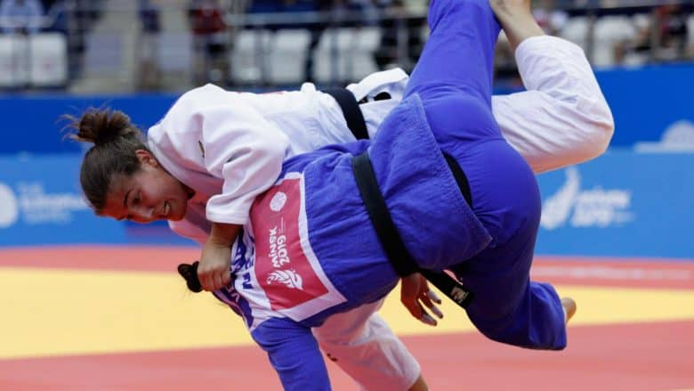Blue and white Judo opponents throwing each other toward ground