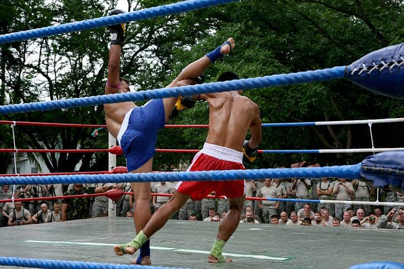 Two Muay Thai kickboxers one with blue shorts kicking one with red shorts in outdoor ring