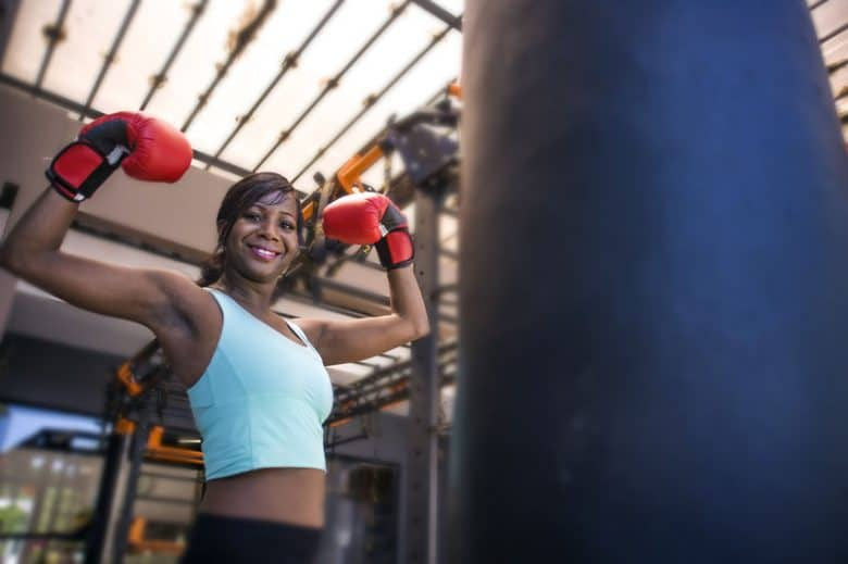 Young attractive black woman wearing boxing gloves flexing muscles next to a heavy bag