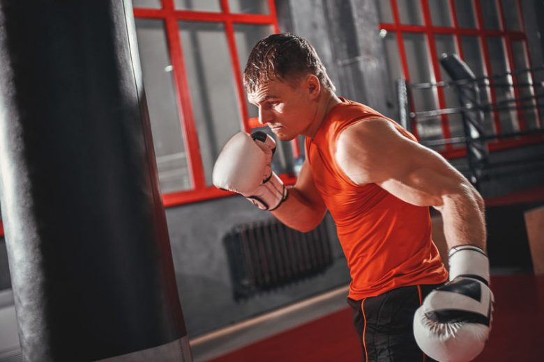 Man in orange shirt and white boxing gloves preparing to hit a black heavy bag