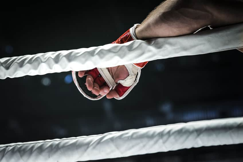 Hand in red and white MMA sparring glove resting on the ropes of a ring