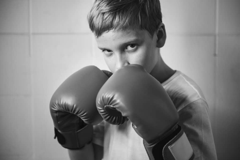 Black and white photo of boy wearing boxing gloves
