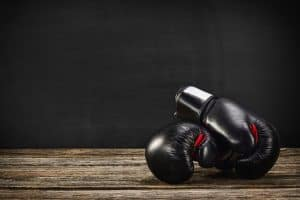Two black boxing gloves resting on old wooden floor with black chalkboard in background