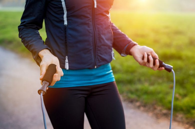 mid section view of woman in blue jacket and dark bottom holding a skipping rope in her hands