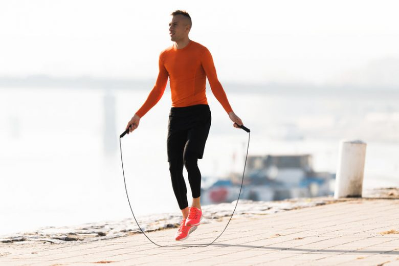 Handsome young man in orange top and black bottoms and orange shoes skipping rope next to water