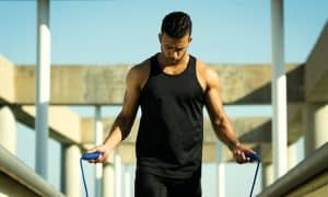 Man in dark sleeveless shirt with muscles getting ready to jump rope
