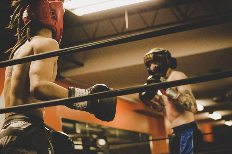 two white men in ring ready to spar one with black headgear one with red blackgear both with black gloves