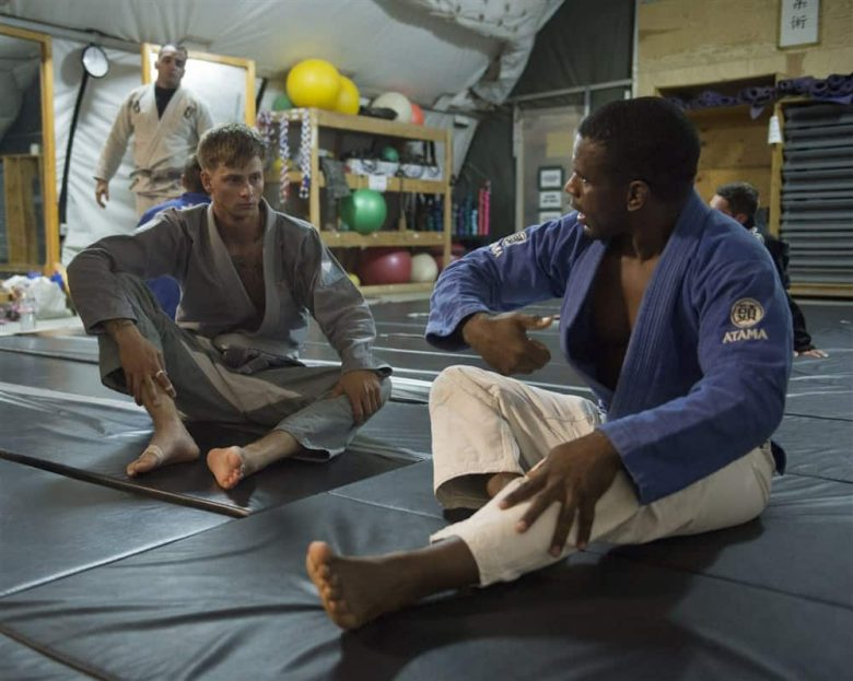 A black man in Blue and white Gi instructing a younger white man in grey gi on BJJ