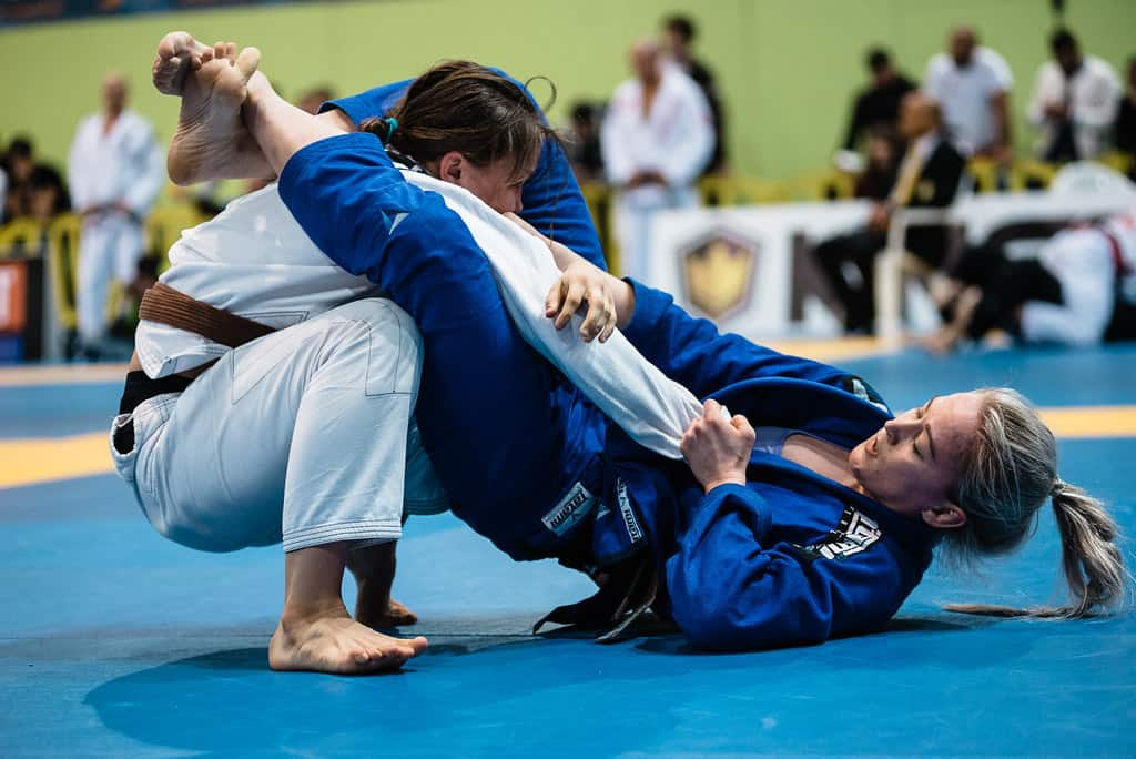 One woman in white gi on top of woman in blue gi