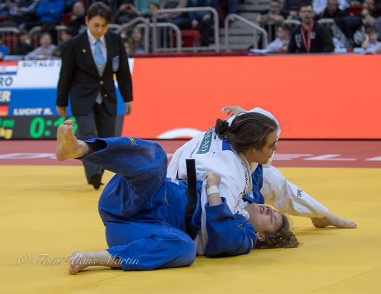 Two women in Judo match, one in blue gi and the other in white gi