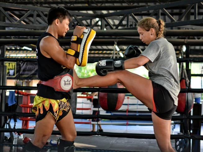 Women kicking a Muay Thai trainer with stomach and focus pads