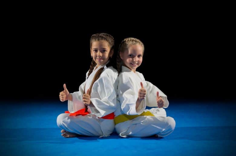 Two little girls in white gi one with orange belt and the other with yellow belt sitting with thumbs up