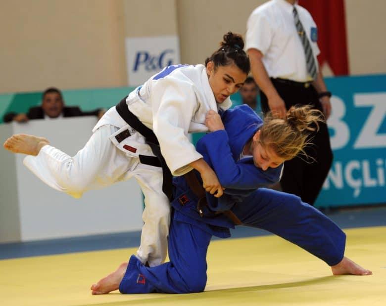 Two women in judo match one in blue gi is throwing teh one in white gi with black belt