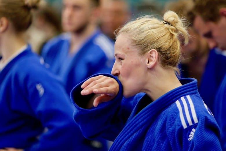 Blonde woman in blue Adidas Judo Gi wiping mouth