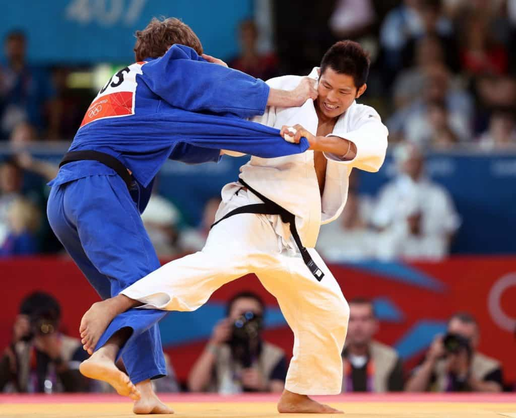 Two men in Judo match one in blue gi the other in white gi